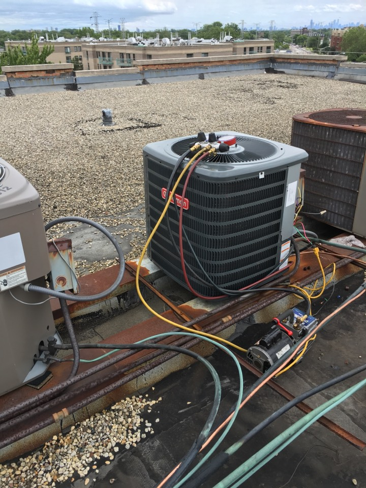 Installing a Goodman condenser on a roof in Skokie. in Howard St, Skokie, IL, USA.